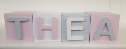 Light grey white and pink painted pine blocks